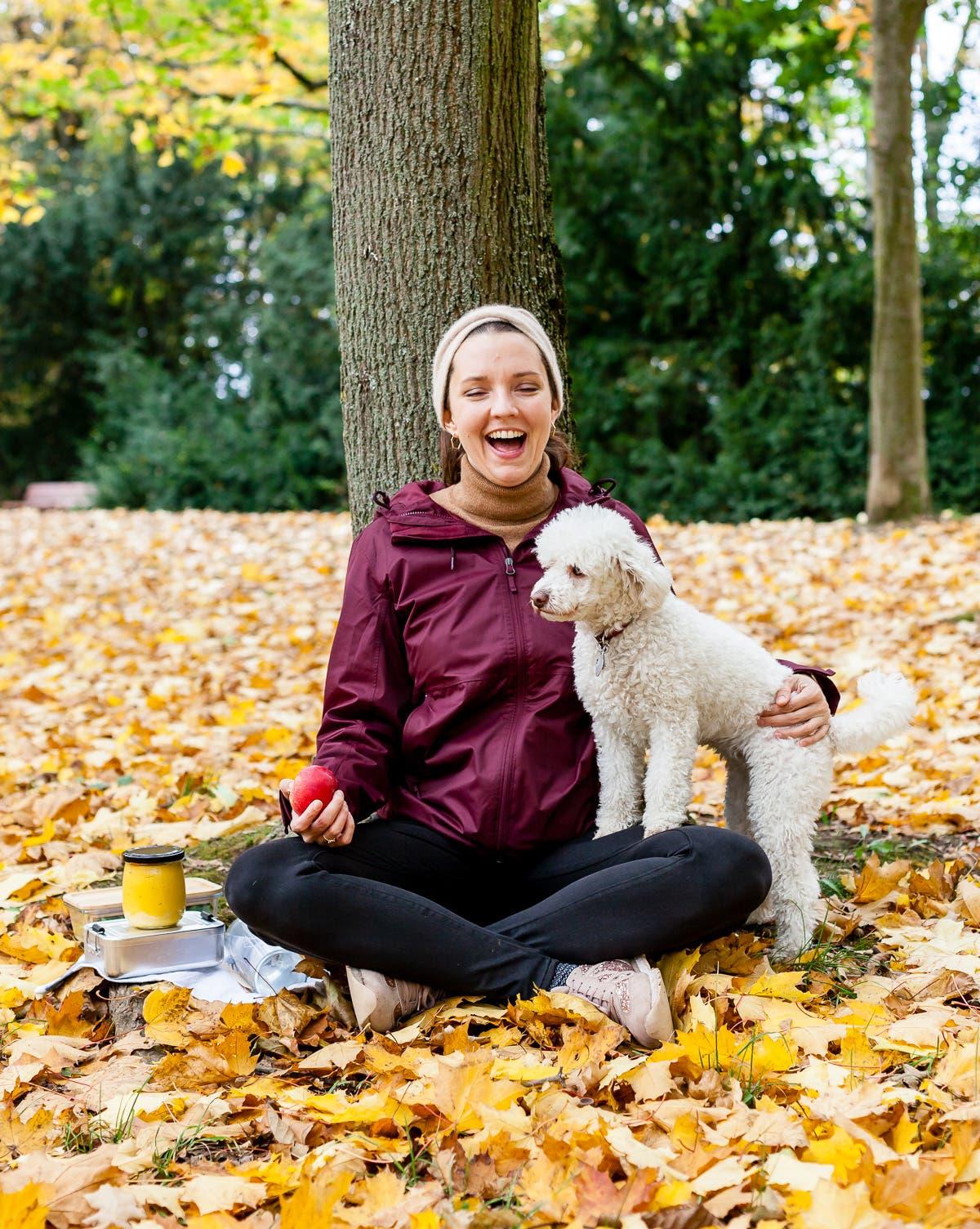 Frau sitzt an einen Baum gelehnt im Herbstlaub und streichelt lächelnd ihren Pudel.