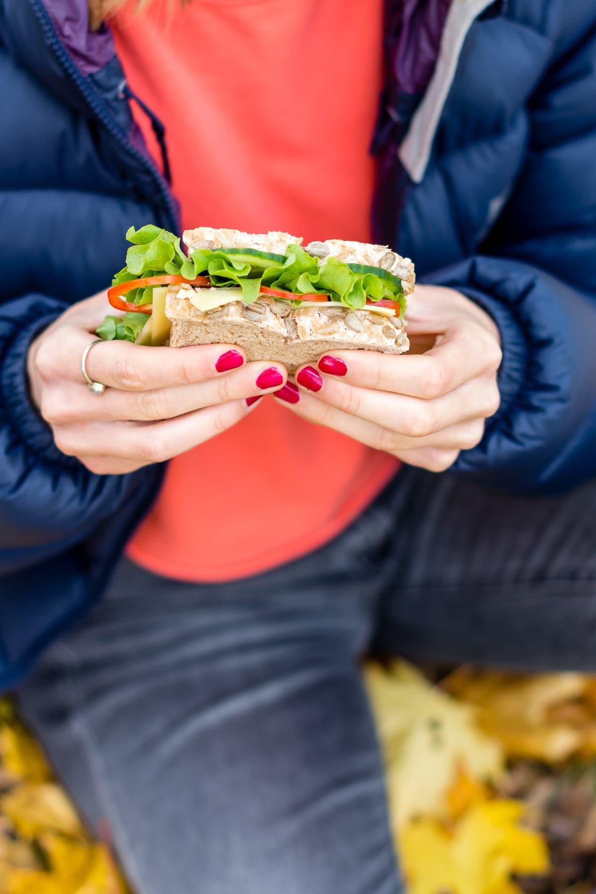 Person hält ein mit Salat und Gemüse belegtes Brot für unterwegs in den Händen.
