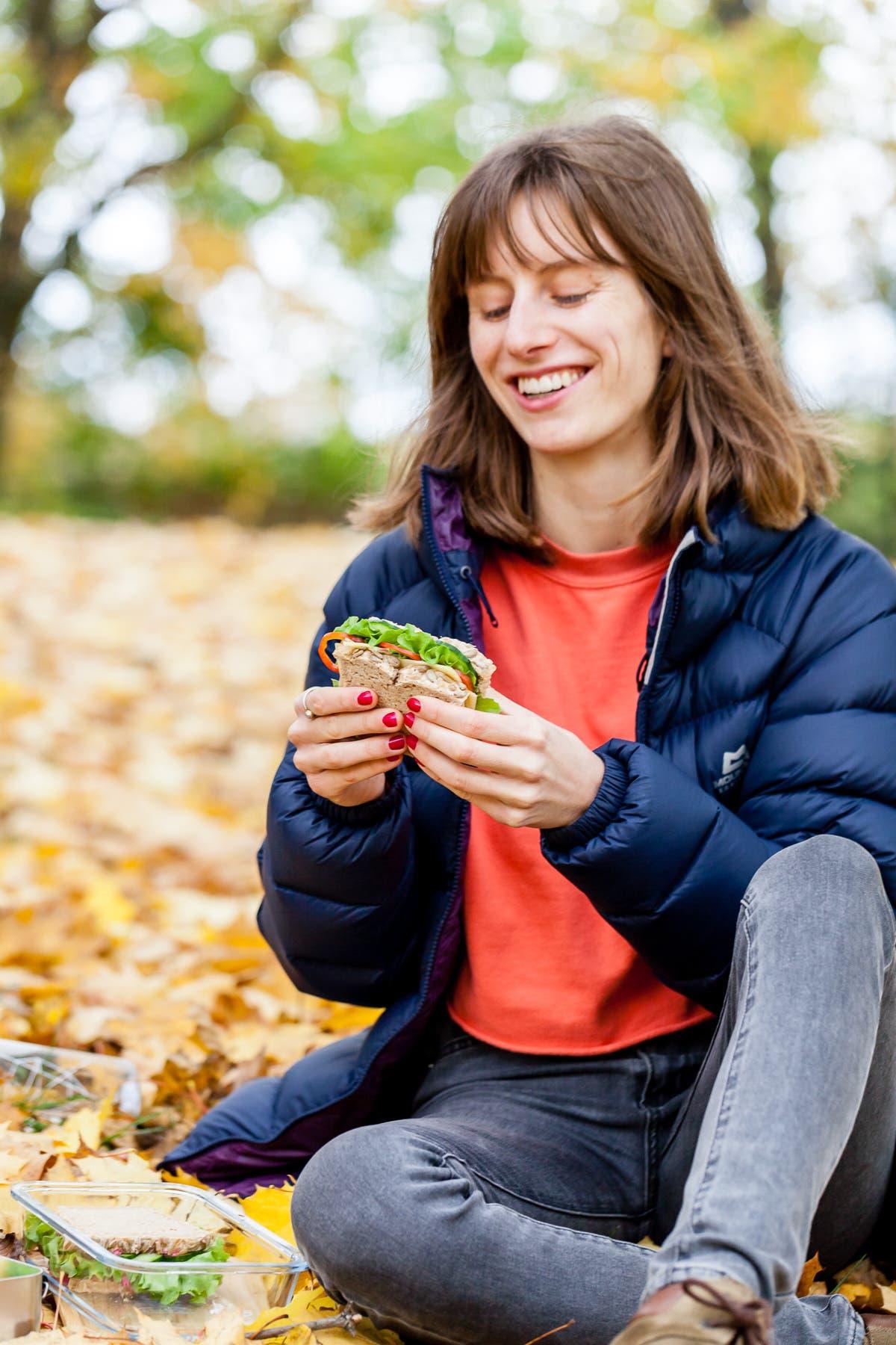 Frau hält ein mit Käse und Salat belegtes Sandwich in der Hand und schaut lächelnd auf das Brot.