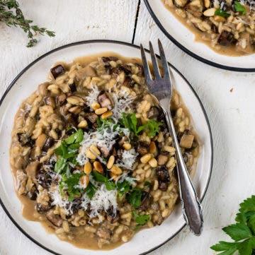 Topshot von einem Teller mit cremigem Pilzrisotto, Kräutern und Parmesan.