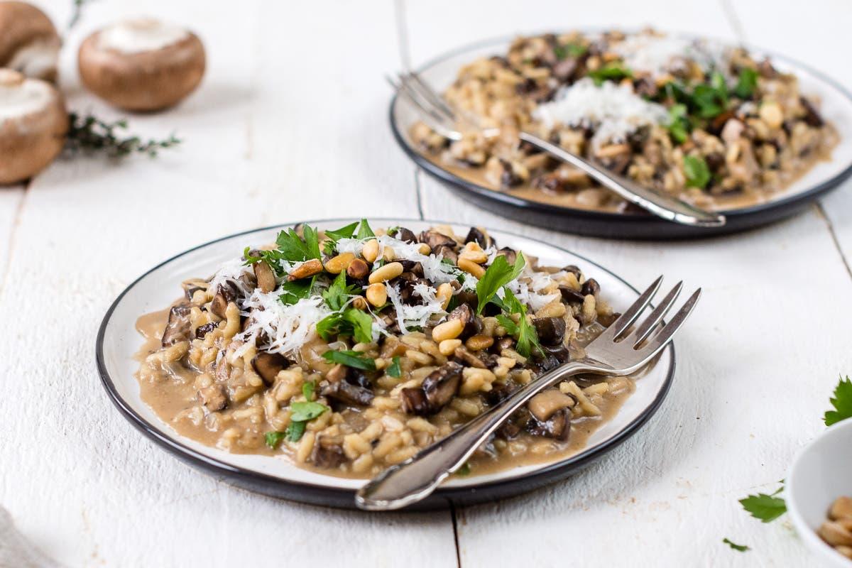 Teller mit cremigem Pilzrisotto, Kräutern und Parmesan.