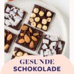 Teller von oben mit selbstgemachter Schokolade mit verschiedenen Nüssen und Früchten.
