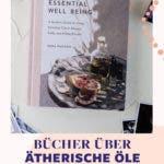 Buch über essential well being, ein ätherisches Öl in einer dunklen Flasche und verschiedene Postkarten.
