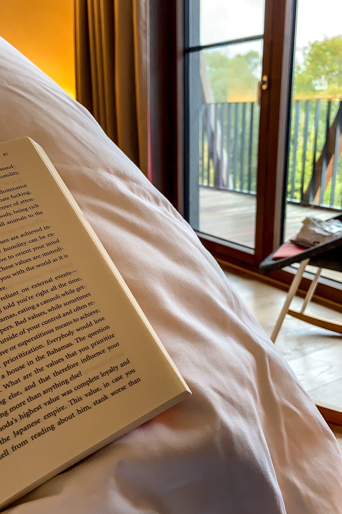 Person sitzt im Bett und liest ein Buch.