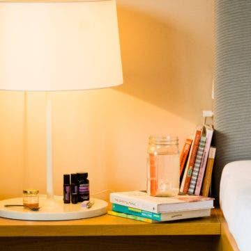 Tisch neben einem Bett mit einer Lampe, Büchern und einem Glas Wasser.