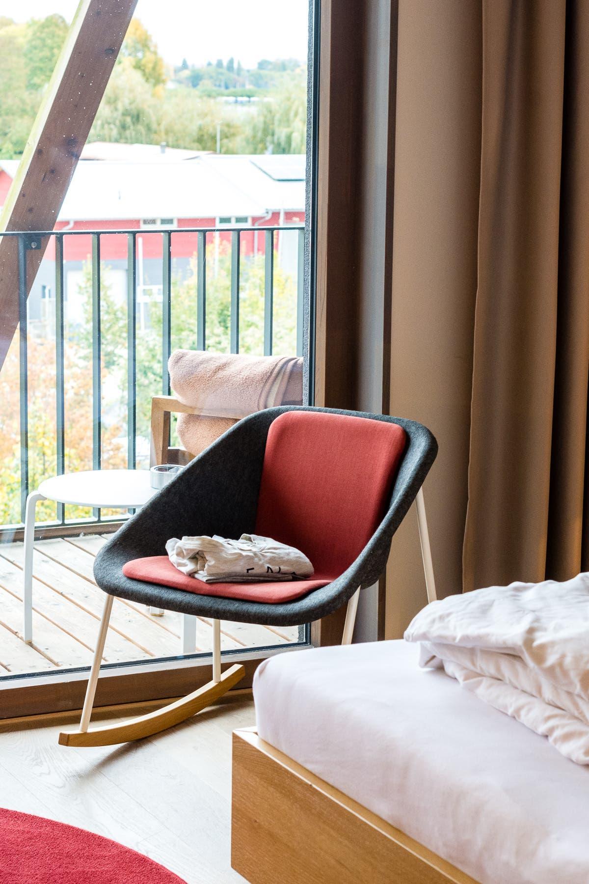 Schaukelstuhl vor einem bodentiefen Fenster mit Balkon.
