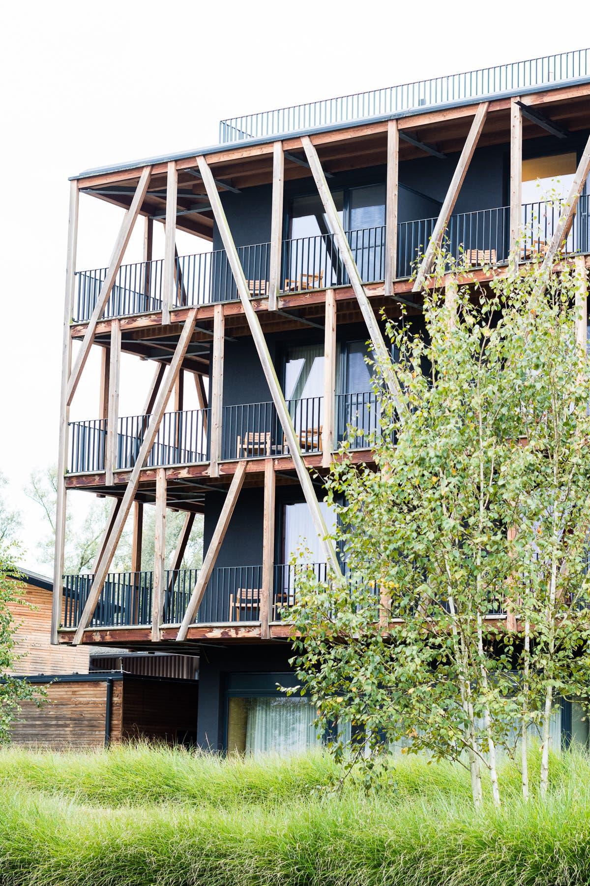 Wellnesshotel mit Holzfassade und einem Baum davor.