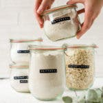 Hände halten ein Glas mit Hafermehl fest. Dahinter stehen weitere Bügelgläser mit glutenfreien Mehlsorten.