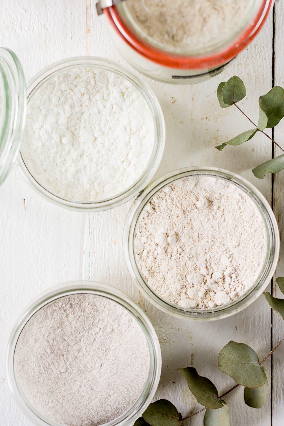 Topshot von Gläsern und verschiedenen glutenfreien Mehlsorten.