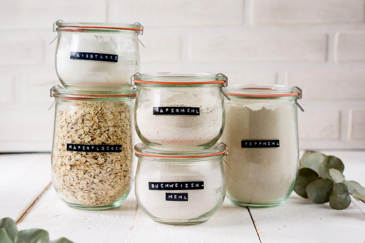 Verschiedene Bügelgläser mit Mehl und Haferflocken gestapelt.