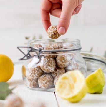 Zitronige Energiebällchen gestapelt in einem Glas und Hand, die ein Bällchen hält.