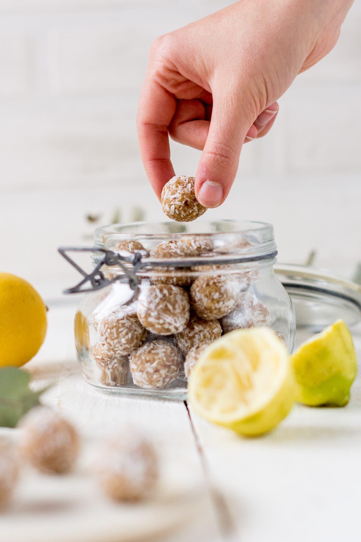 Zitronige Energiebällchen gestapelt in einem Glas und Hand, die ein Bällchen hälthen hält