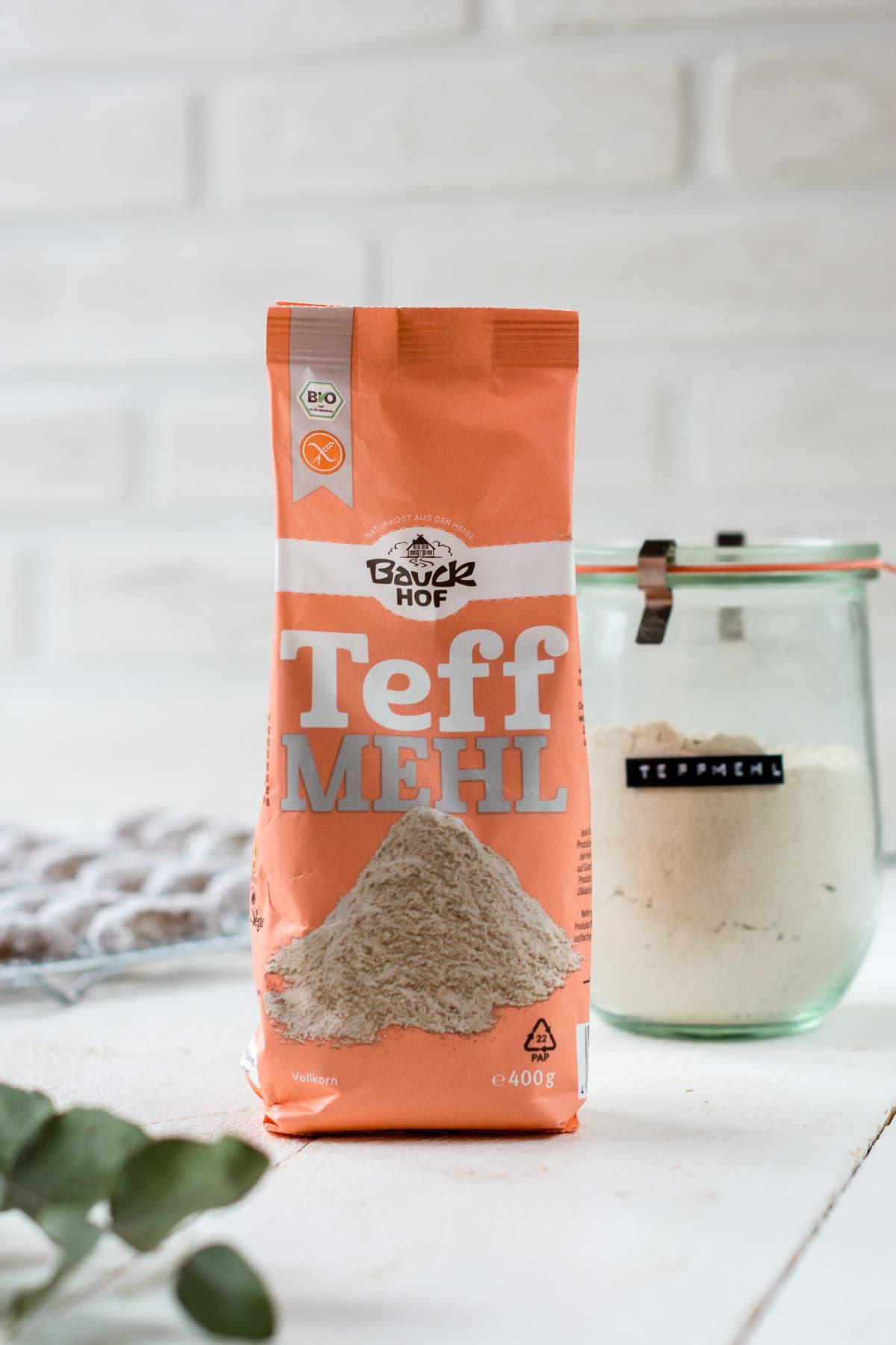 Verpackung eines glutenfreien Mehls auf weißem Untergrund und einem Glas mit Teffmehl.