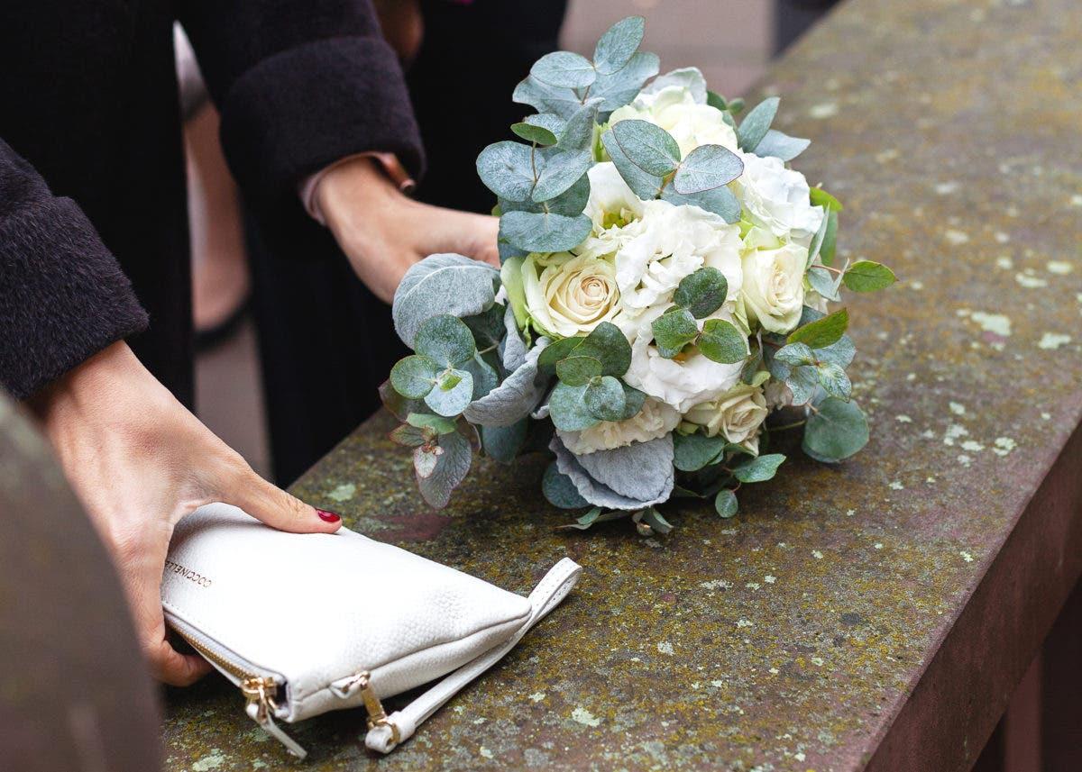 Person hält in der einen Hand einen Brautstrauß und in der anderen eine helle Handtasche.