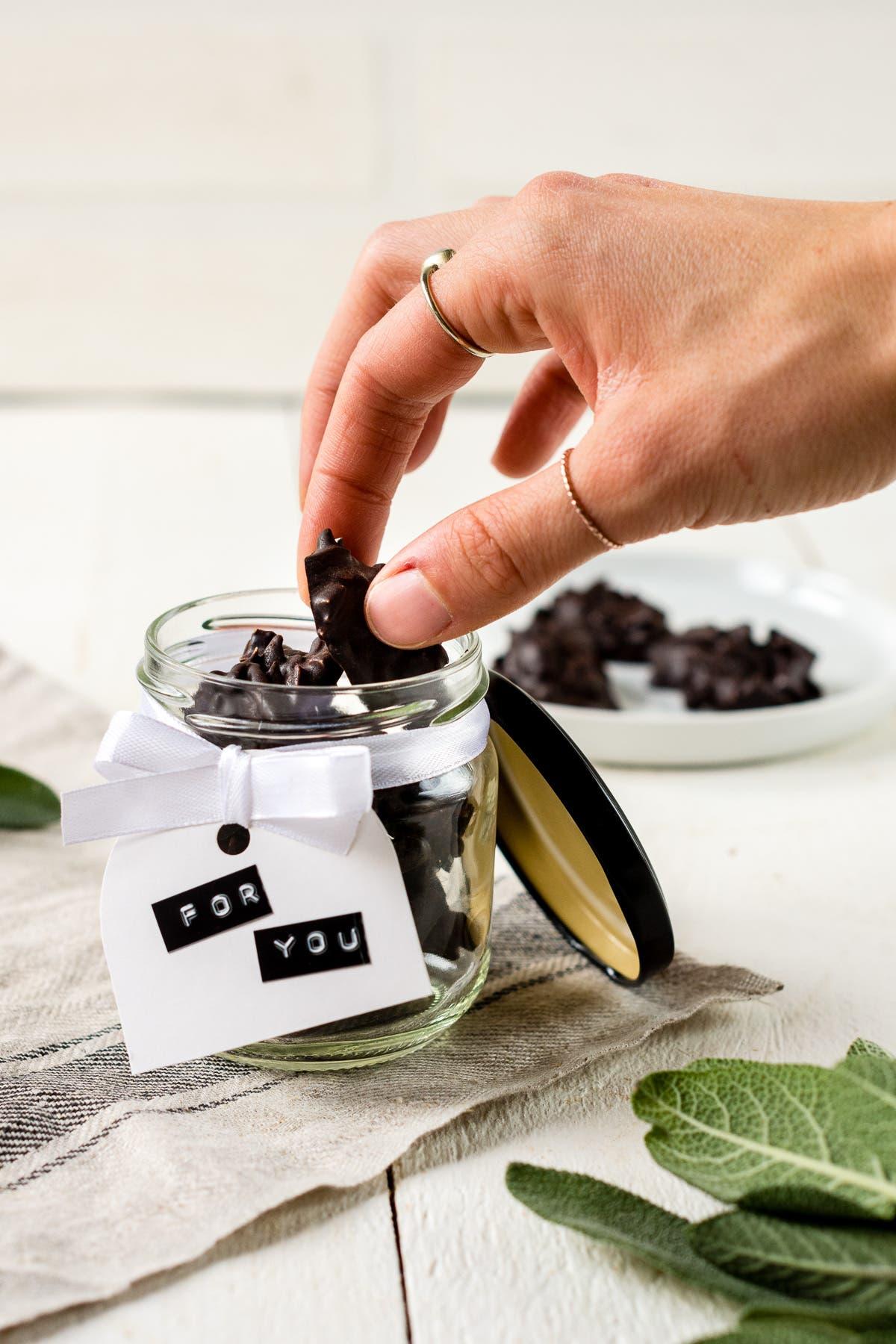 Hand nimmt ein Stück selbstgemachte Schokoladen Mandelsplitter aus einem Glas.