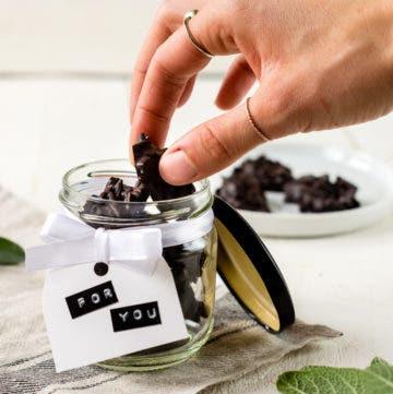 Hand nimmt ein Stück Schokoladen Mandelsplitter aus einem Glas.