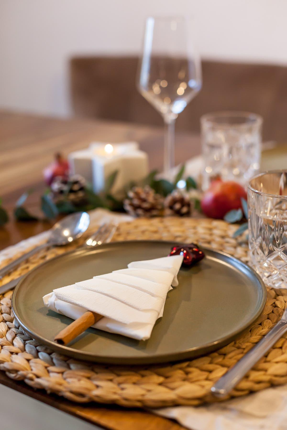 Vegetarisches Weihnachtsmenü mit weihnachtlich dekoriertem Teller mit einem Tannenbaum aus Servietten und Zimt. Im Hintergrund Weihnachtsdekoration und Gläser.