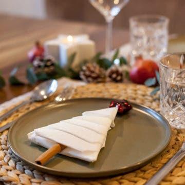 grauer Teller mit einem Tannenbaum aus Servietten und einer Zimtstange, im Hintergrund stehen Gläser und Weihnachtsdekoration.