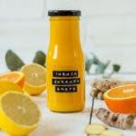 Flasche gefüllt mit Orangen Ingwer Shot und frische Orangen und Ingwer.