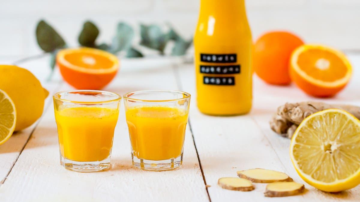 Zwei Gläser gefüllt mit Orangen Ingwer Shot und frischen Orangen und Ingwerscheiben.