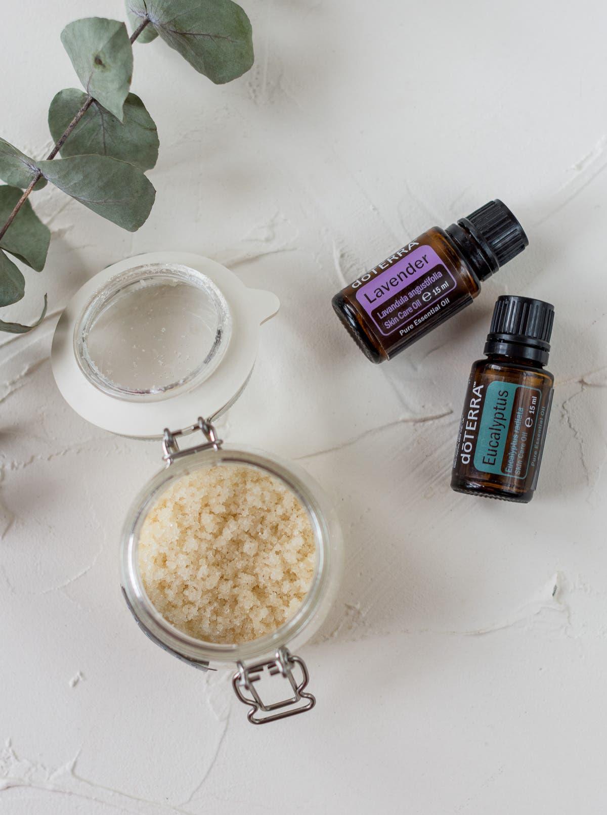 Topshot des selbstgemachten Zuckerpeelings in einem Bügelglas mit den ätherischen Ölen Lavendel und Eukalyptus daneben.