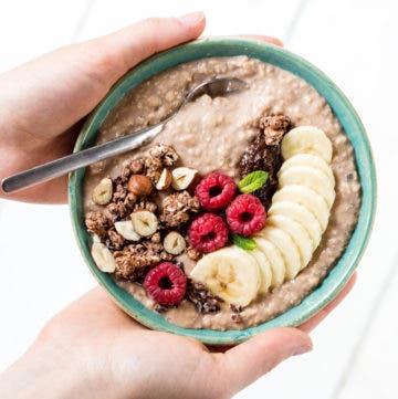 Topshot von einer Schüssel mit Porridge, Beeren, Bananen und Granola.
