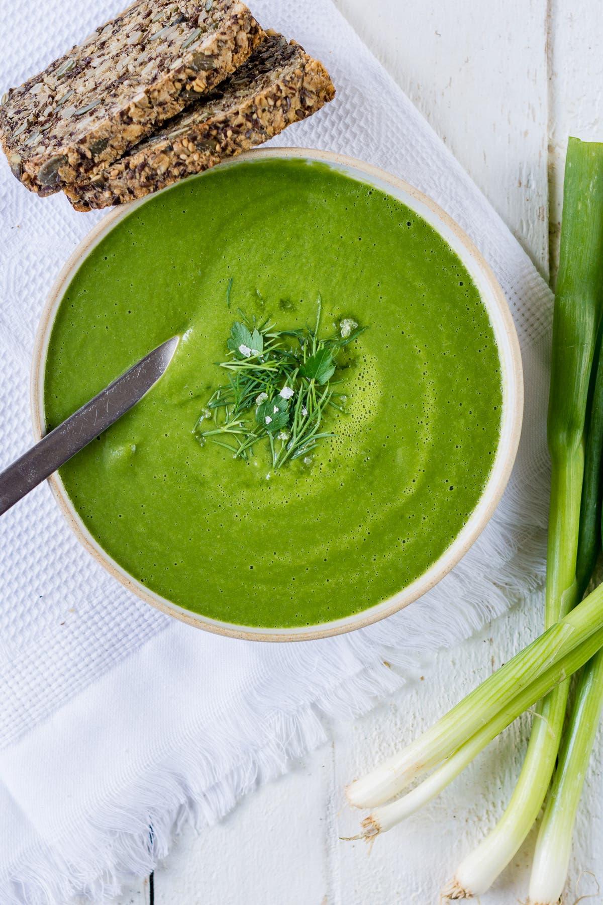 Topshot von Teller mit grüner Detox Suppe und frischen Kräutern mit zwei Scheiben Brot.