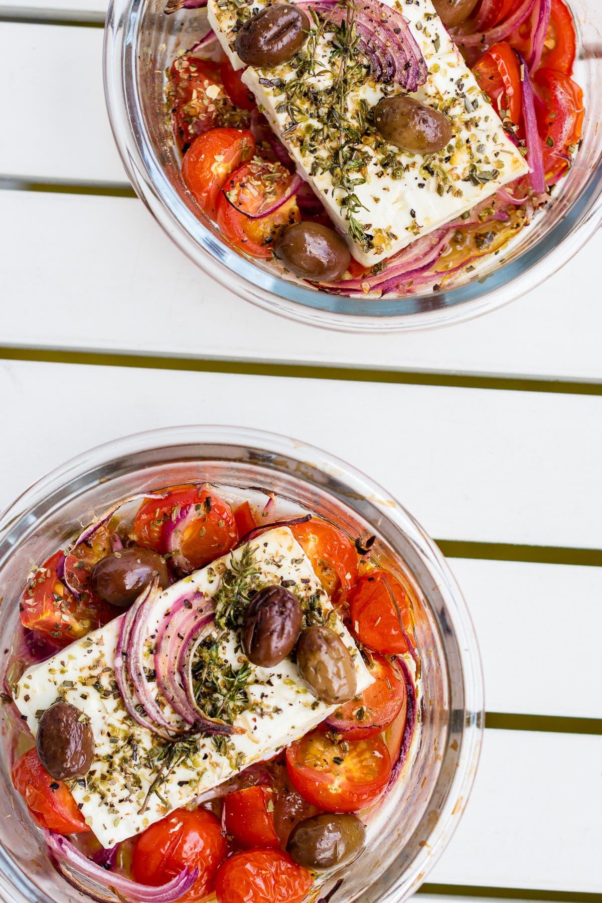 Topshot von zwei Glasschalen mit Tomaten, Zwiebeln, Oliven und mariniertem Feta.