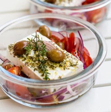 Glasschale gefüllt mit mariniertem Feta, Oliven, Zwiebeln und Tomaten.