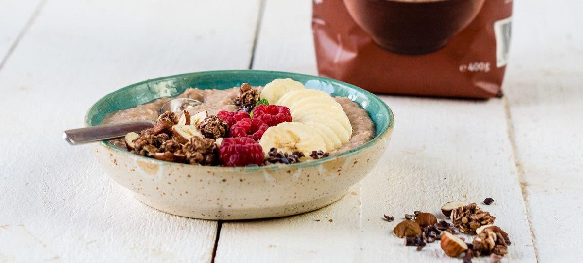 Schüssel mit Porridge und Beeren, Banane und Knuspermüsli.
