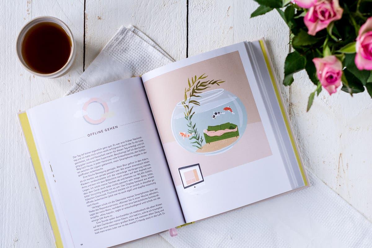 Topshot von aufgeschlagenem Buch auf weißem Untergrund. Daneben ein paar Blumen und eine Tasse Tee.