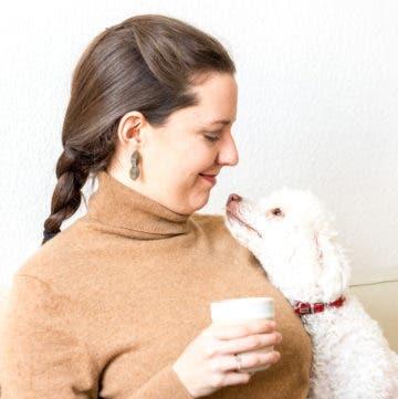 Frau hält eine Tasse in der Hand und schaut ihren Pudel an.