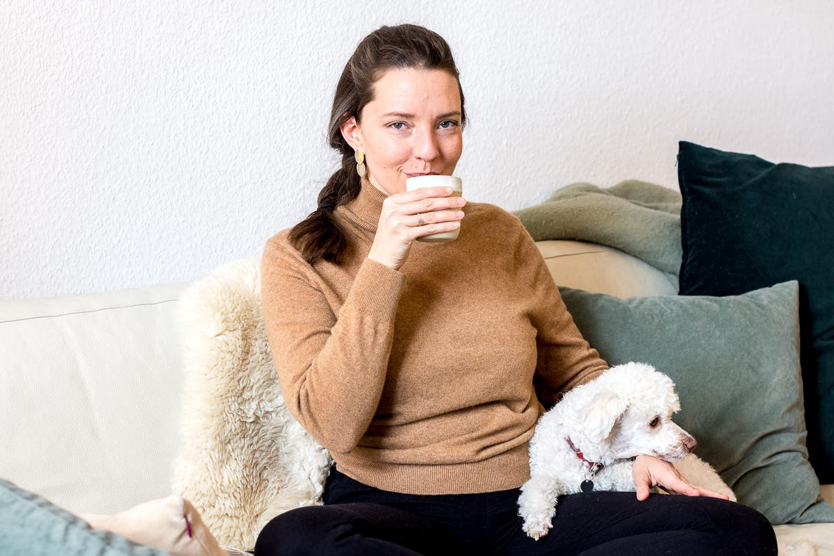 Frau sitzt mit einem Pudel auf der Couch und trinkt aus einer Tasse.