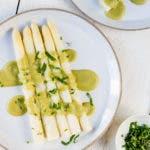 Teller mit weißem Spargel und einer grünen Sauce Hollandaise und Schnittlauch.