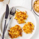 Topshot von Teller mit Besteck und drei Kartoffelpuffern.
