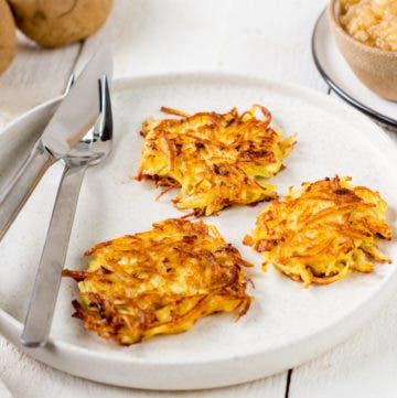 Teller mit Besteck und drei Kartoffelpuffern.
