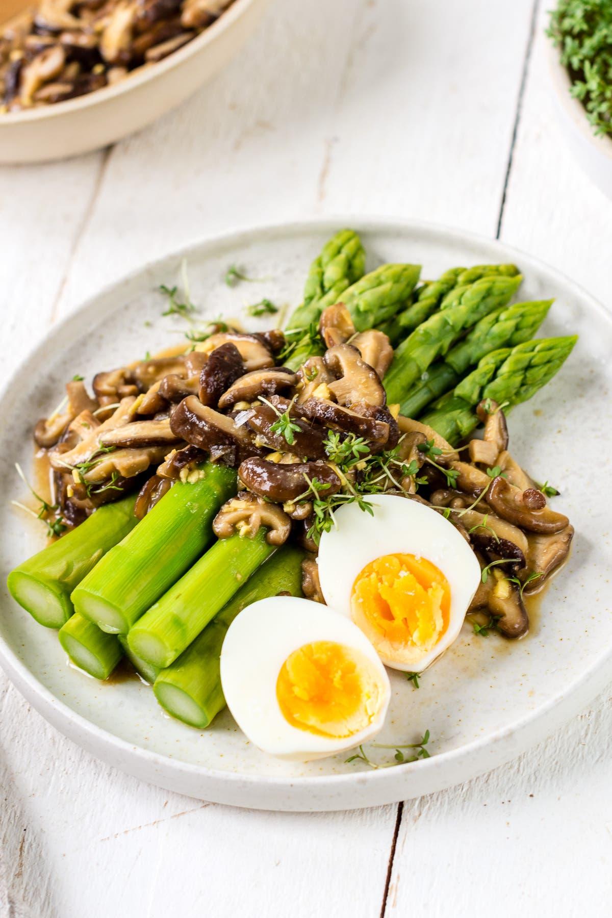 Teller mit Spargelsalat und Pilzen und gekochten Eiern auf einem weißem Teller.